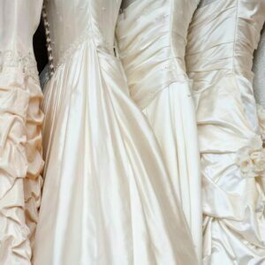 Satin wedding gowns hanging in a row