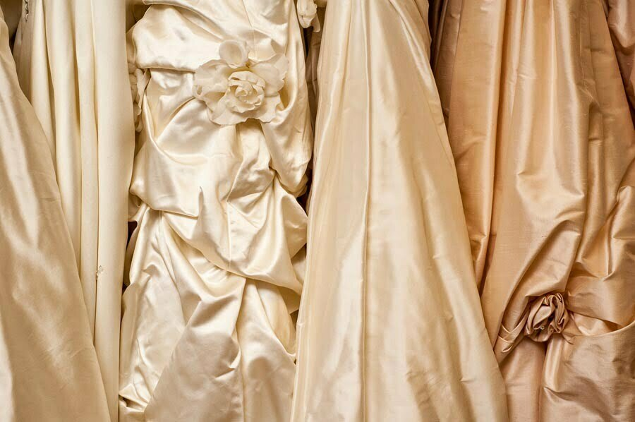 Gold coloured wedding gowns hanging in a row