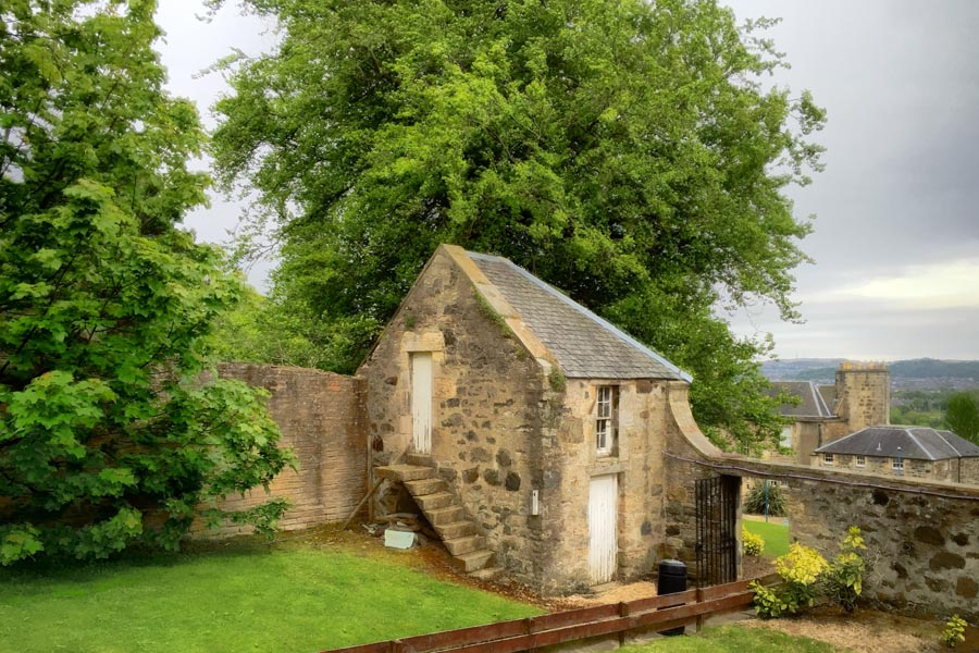 Stone outbuilding in the corner of the grounds of an institution in Scotland