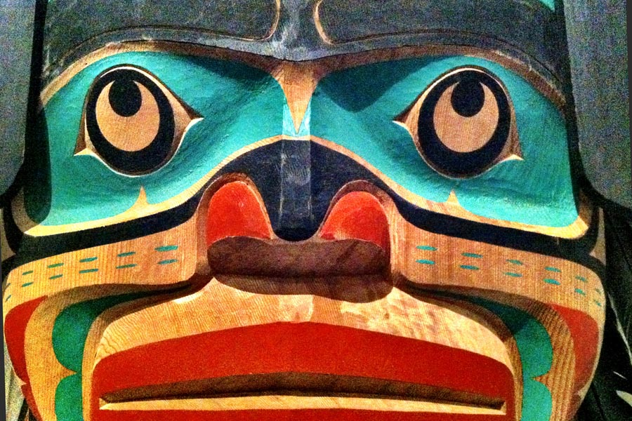 Inuit face with eyes looking up to the sky with nose and wide nostrils - on totem pole in red, green, and natural wood colour
