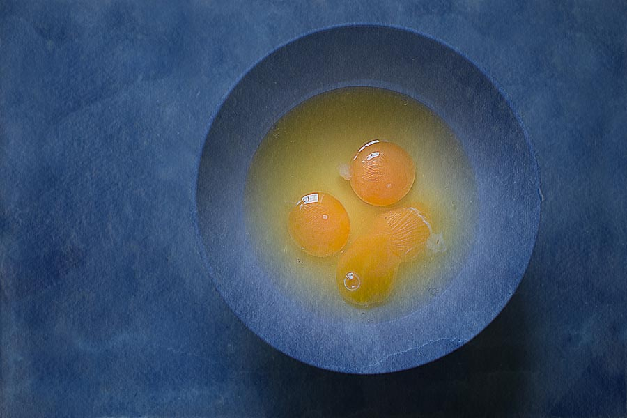 Yellow yolks in a blue bowl with blue background colour