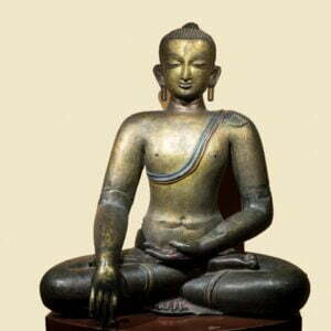Gold metal seated buddha sitting cross legged with one hand and fingers pointing to the Earth and the other palm upwards with string across shoulder