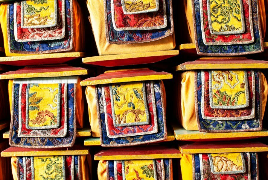 Tibetan Buddhist books wrapped in cloth between boards and stacked in a storeroom in a hotel in Darjeeling