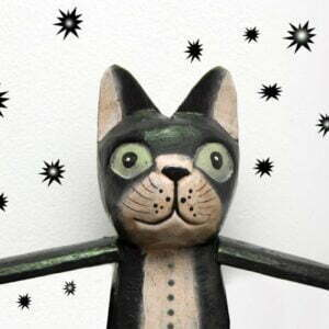 Wooden cat with startled expression with a waistcoat and arms outstretched and bullet holes in the wall behind it
