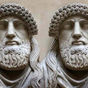 Two Greek grey stone sculpted heads with beards and stylised curly hair and eyes lifted to the heavens