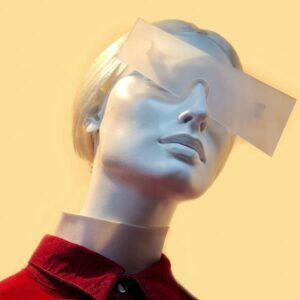 Female mannequin with short stylish hair and red coat with futuristic glasses shaped as a large translucent rectangle