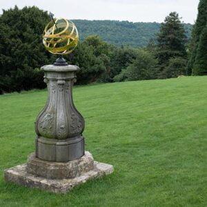 Golden clock worked by the sun - on a pedestal in a garden in the West Country in England with trees behind in the valley and rising onto the hills behind