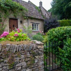 Stone cottage with stone slab roof, roses on the front wall, front garden with pink hydrangeas and stone wall to the street