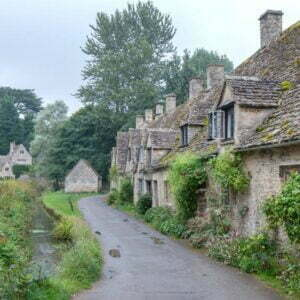 Lane of stone country cottages seen receding into the distance with stone roofs and a small stream or brook facing the cottages