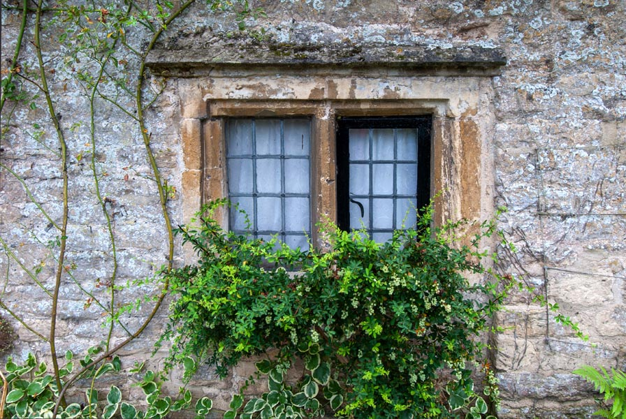 Window in a country cottage in the Cotswolds in England with stone mullions