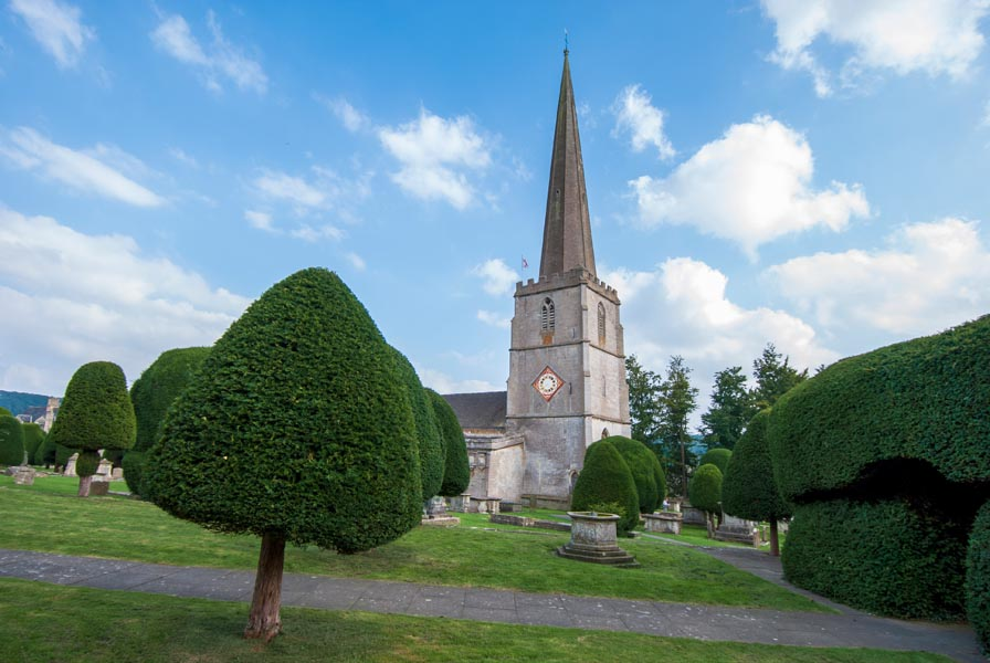 Topiary in an English churchyard with church spire