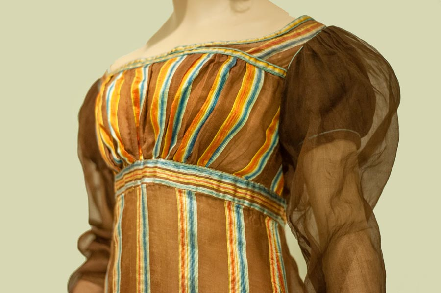 Empire silhouette dress in vertical stripes with multicoloured band below the bust-line and short sleeves overlaid with sheer fabric sleeves to the wrist.