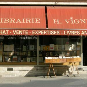 Bookshop in Paris with awning describing its services and books on a trestle table in front of the shop