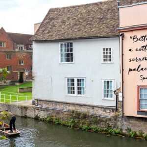 Old buildings by the river with an old Spanish quotation written across the side of one building that 'Better joy in a cottage, than sorrow in a palace.'