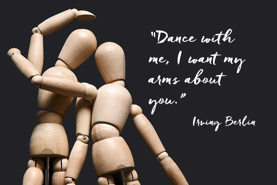 """Two dancing mannequins with their arms entwined, with a quotation from Irving Berlin """"Dance with me, I want my arms about you."""""""